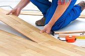 picture of carpenter  - carpenter worker installing laminate flooring in the room - JPG