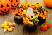 stock photo of candy  - Halloween cupcakes and candy on wooden table - JPG