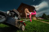 foto of grass-cutter  - Beautiful laughing housemaid with lawn mower near country house - JPG