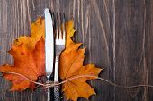 stock photo of knife  - Knife fork and yellow autumn leaves on the wooden table - JPG