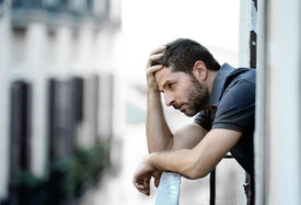 stock photo of emotion  - Lonely young man outside at house balcony looking depressed destroyed sad and suffering emotional crisis and grief on an urban background - JPG