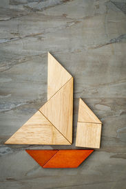 stock photo of tangram  - abstract picture of a sailing boat built from seven tangram wooden pieces over a slate rock background - JPG