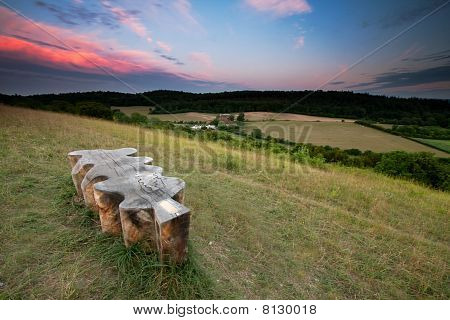 Sunset Lit Clouds over Green Fields and a Bench