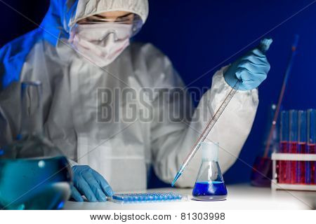 science, chemistry, biology, medicine and people concept - close up of young female scientist with pipette and flask making test or research in clinical laboratory