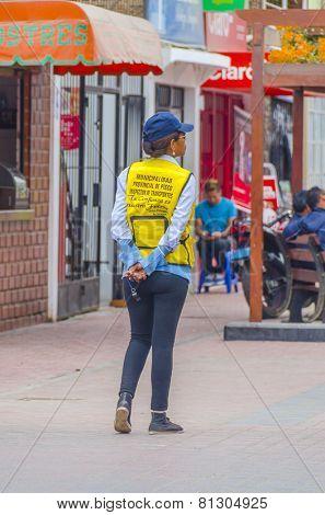 PISCO, PERU, MAY 21, 2014: Female transport inspector patrols street