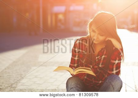 Portrait of a young hipster woman enjoying a good book sitting at sunny evening outdoors