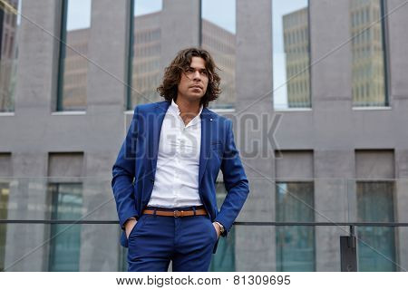Portrait of handsome executive standing near office building with hands in his pockets