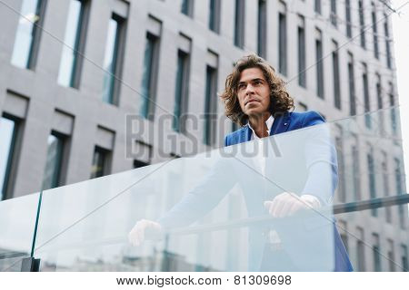 A determined well dressed businessman standing out in the city looking away