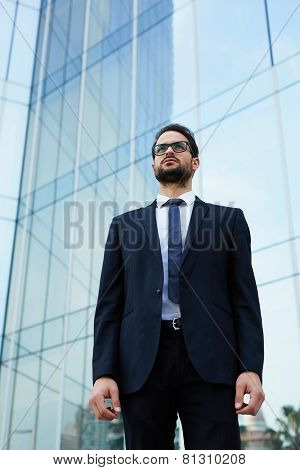 Half length portrait of serious handsome businessman at office building