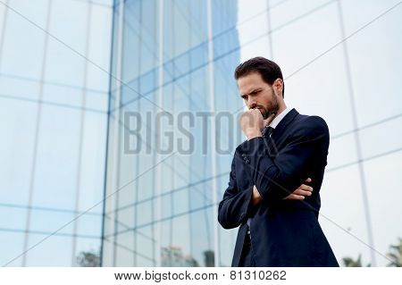 Handsome concentrated business man standing with arm crossed and hand against his mouth