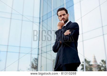 Pensive businessman standing with arm crossed and hand against his mouth looking away