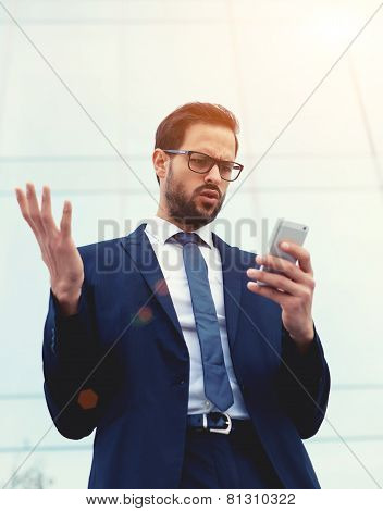 Handsome unhappy surprised and shocked executive looking at smart phone receiving bad news