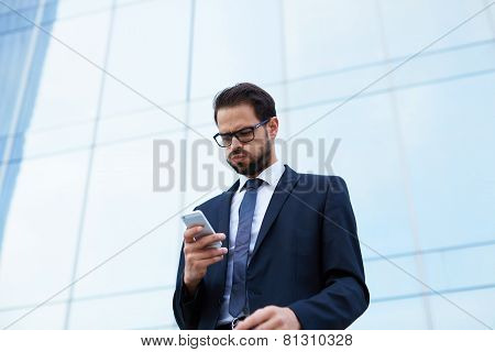 Despairing businessman reading text message while holding mobile phone