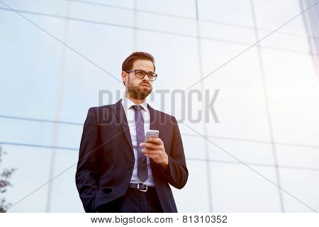 Handsome businessman receiving shocking news as he reads a text message on mobile phone