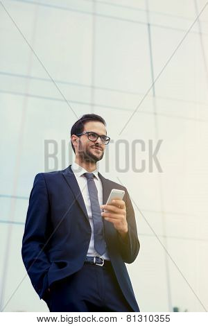 Satisfied businessman receiving good results of last project with mobile phone
