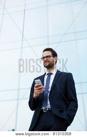 Handsome businessman in suit and eyeglasses holding cell phone smiling