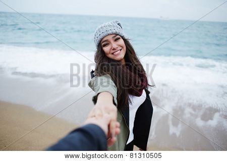 Portrait of attractive enamored woman walking hand in hand with her boyfriend on the beach