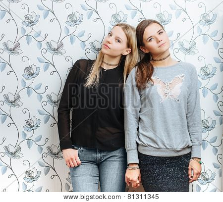Lifestyle portrait of two young best friends hipster women holding hands indoors