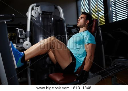 Full lengt portrait of muscular build man doing legs press exercise in fitness center