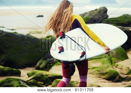Professional surfer girl walking to the ocean holding her surfboard