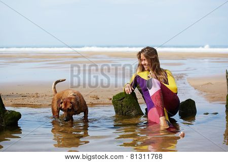 Surfer girl in wets suit playing with dog lying on wet sand taking a break sitting against the ocean