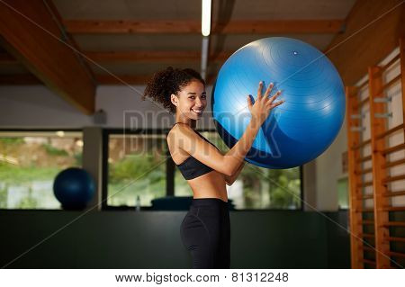 Young cheerful afro woman standing with fit ball in fitness center attractive girl smiling at gym.