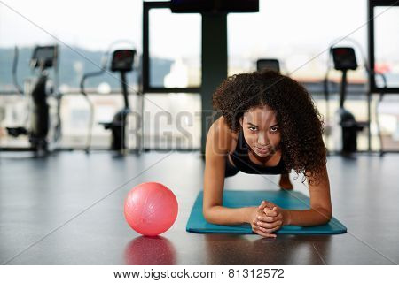 Attractive dark skinned girl exercising at fitness training at gym