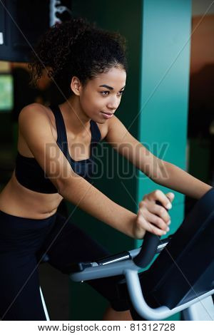 Attractive sexy woman with perfect figure riding on spin bike at fitness center