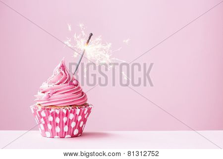 Pink cupcake decorated with a sparkler
