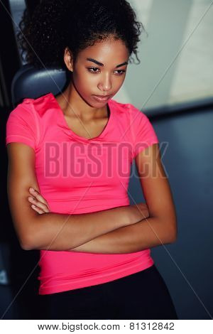 Portrait of young afro american woman wearing pink t-shirt relaxing after workout