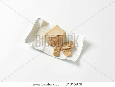 crumbled block of compressed fresh yeast in its wrapper