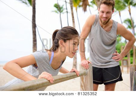 Fitness instructor coaching and helping woman doing push-ups on cross fit horizontal bar station on beach. Arm press pushups easy exercises.