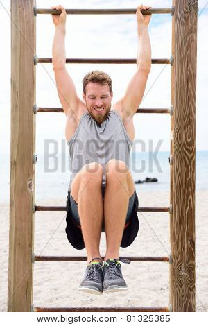 Fitness people - man training abs by lifting legs on cross fit bar rack outside on outdoor gym station.