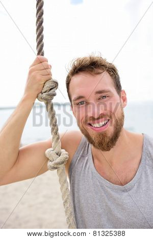 Fitness people portrait - healthy man with rope. Happy adult on summer beach showing climbing rope used in crossfit workout for strength training.