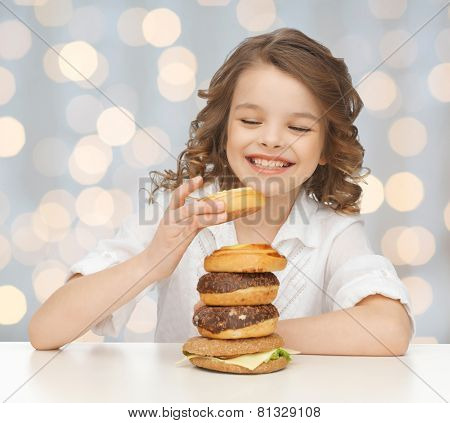 junk food, unhealthy eating, children and people concept happy smiling girl eating buns, donuts and burger over holidays lights background