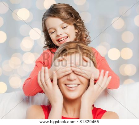 people, happiness, leisure, family and motherhood concept - happy mother and daughter playing guess who game over holidays lights background