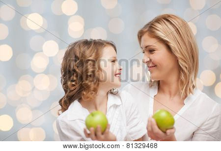people, family, healthy eating and parenting concept - happy mother and daughter with green apples over lights background