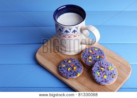 Three glazed cookies with cup of milk on cutting board and color wooden planks background
