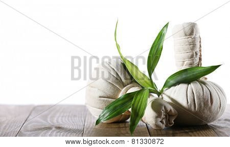 Spa compress balls with green leaves isolated on white