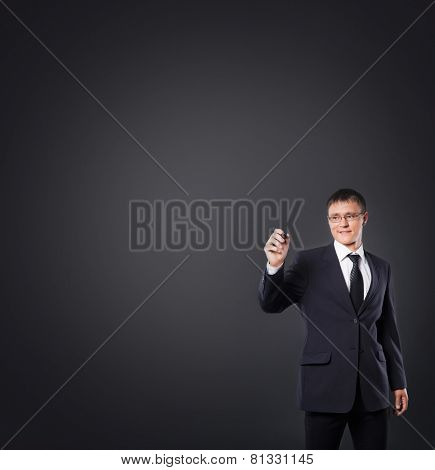 Successful and smart businessman writing imaginary text over grey background. Wide blank space to place any text.