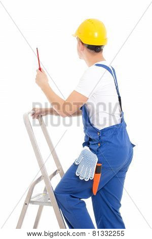 Back View Of Young Man Builder In Blue Coveralls With Screwdriver On Ladder Isolated On White