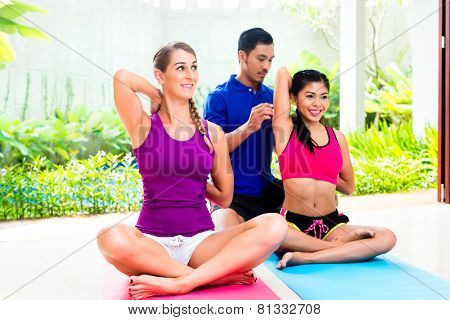 Fitness people, Women and personal trainer of mixed ethnicity, at fitness exercise in front of tropical garden with pool