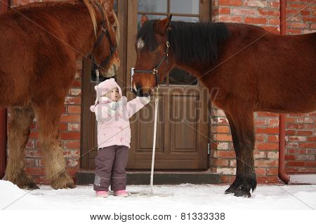Little Girl And Two Horses Standing Near The Cottage Door