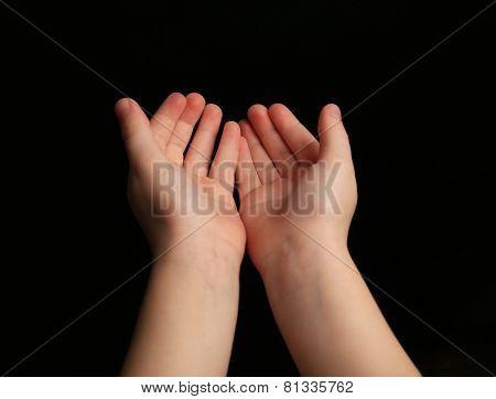 Child hands on black background