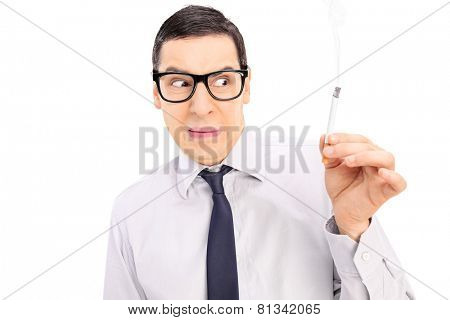 Disgusted man holding a cigarette isolated on white background