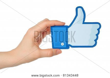 Hand holds facebook thumbs up sign