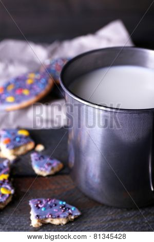 Crumbled glazed cookies on sheet of paper with metal mug of milk on rustic wooden planks background