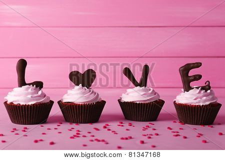 Delicious Valentine Day cupcakes on pink wooden background