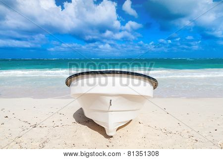 White Pleasure Motor Boat Lays On Sandy Beach. Front View