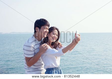 Portrait Of Young Man And Woman Selfie ,self Portrait By Mobile Phone In Relaxing Emotion Sea Beach